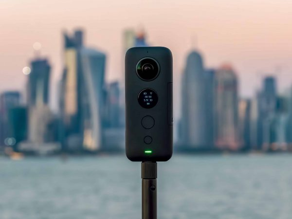 Doha, Qatar – February 2019: Insta360 One X 360 camera on a tripod with cityscape in the background