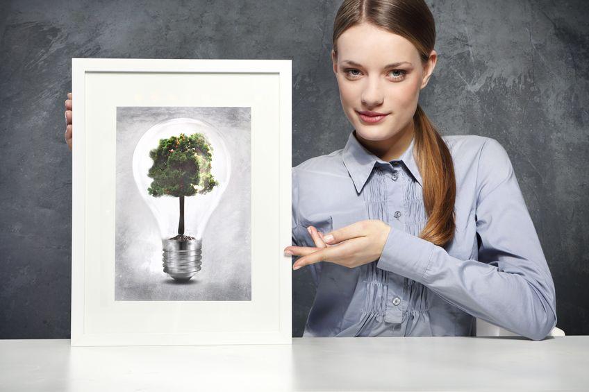 Mujer mostrando cuadro de bombilla que encierra a un árbol
