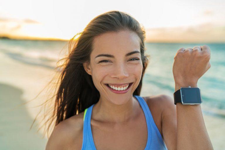 Mujer en la playa con smartwatch