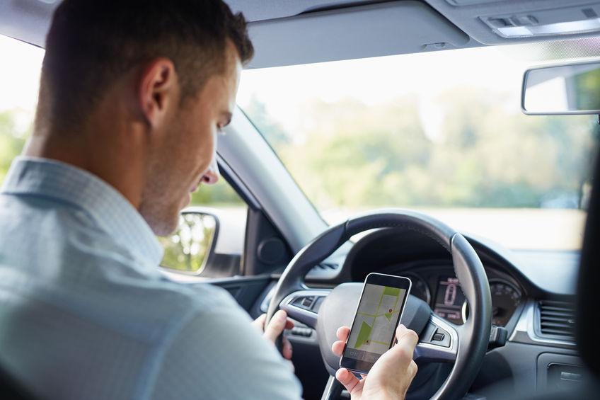 Hombre en auto revisando su GPS en móvil