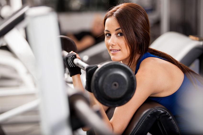 Mujer en gimnasio utilizando guantes para hacer ejercicio