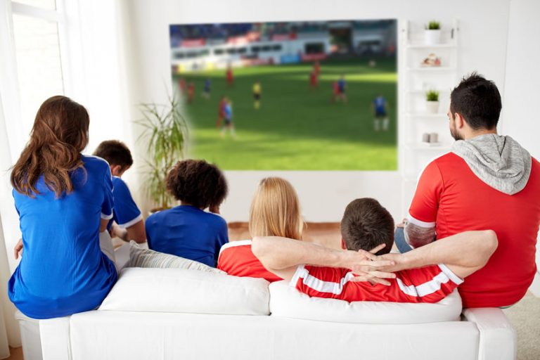 Un grupo de amigos viendo el fútbol en un proyector