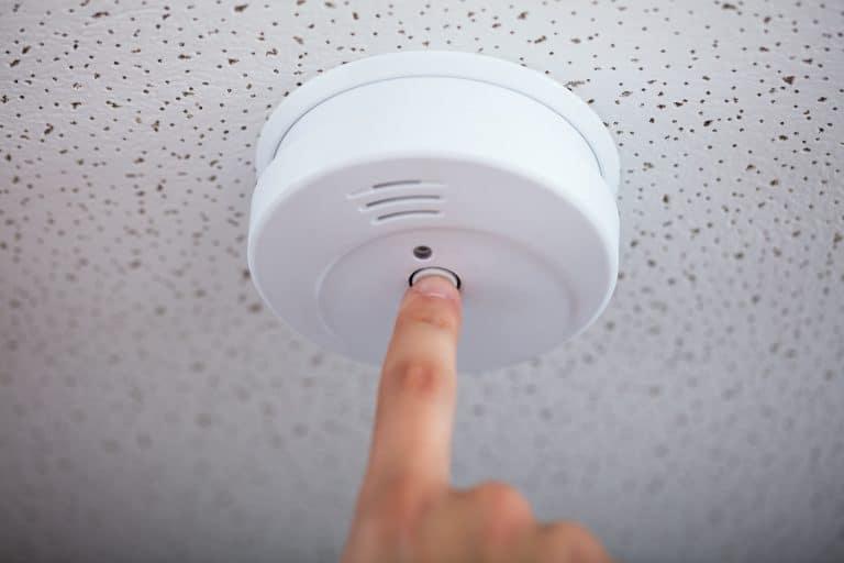 Una persona desactiva un detector de humos