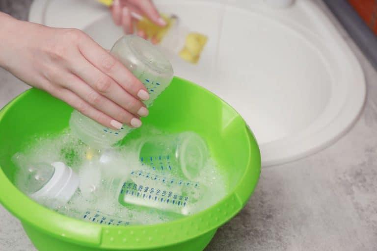 Una persona lavando biberones