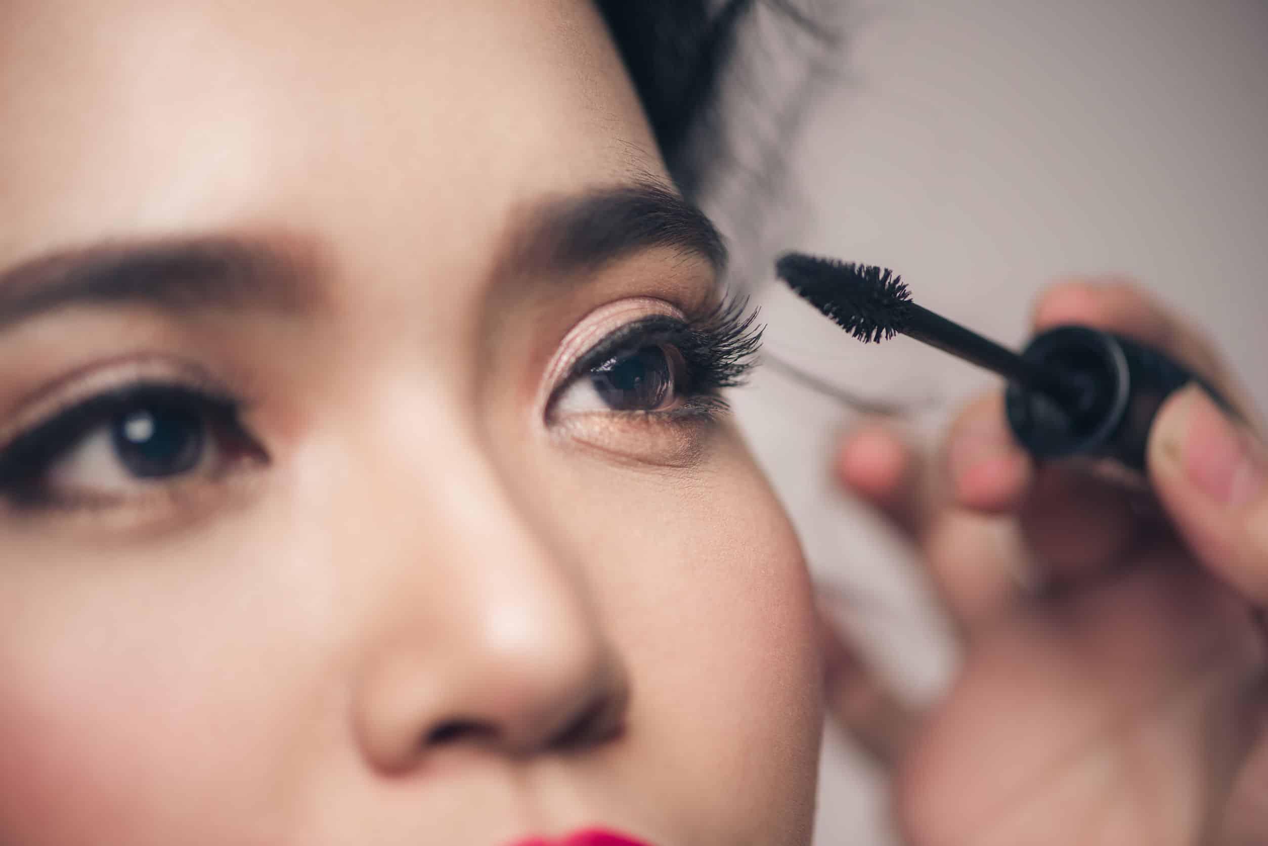 Mujer aplicando se mascara de pestaña