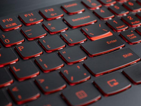 Closeup of gamer laptop keyboard red illumination, backlit keyboard, english letters.