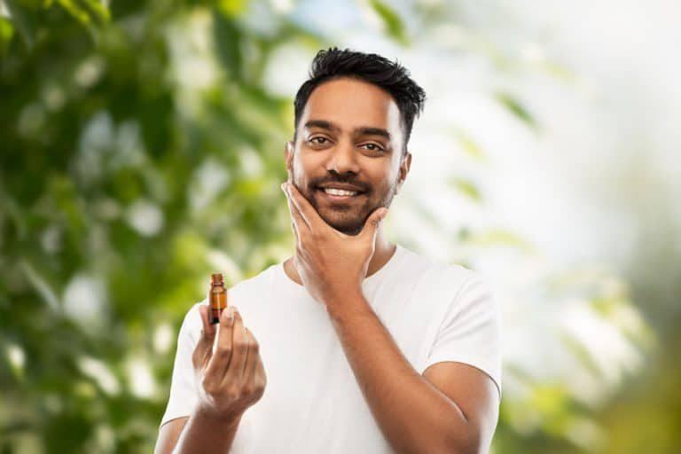 Chico aplicándose aceite en la barba