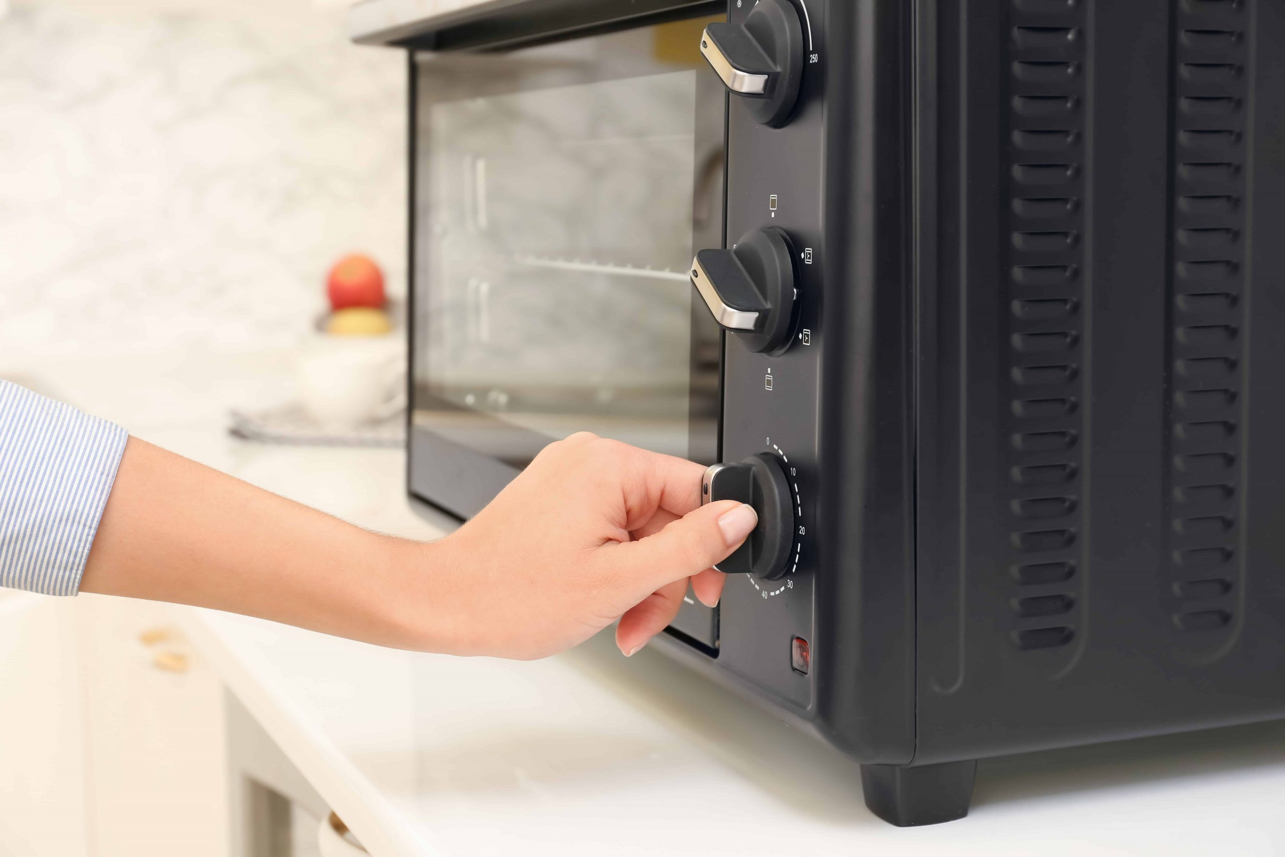 Una mano activando un horno de convección