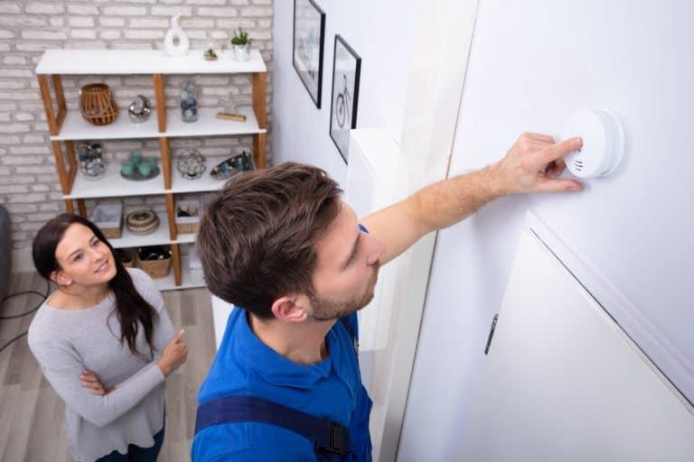 Una mujer y un técnico instalando un detector de humos