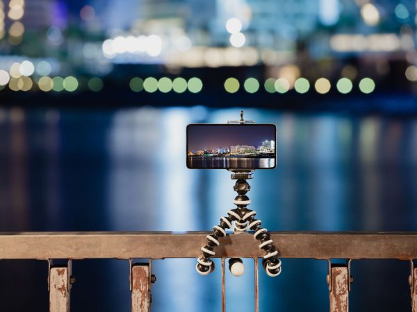 Using smartphone on flexible foldable mini tripod to making the photo of city night lights reflected on a sea surface