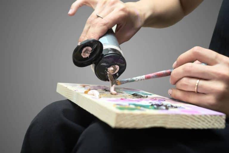 Una mujer aplicando pintura acrílica