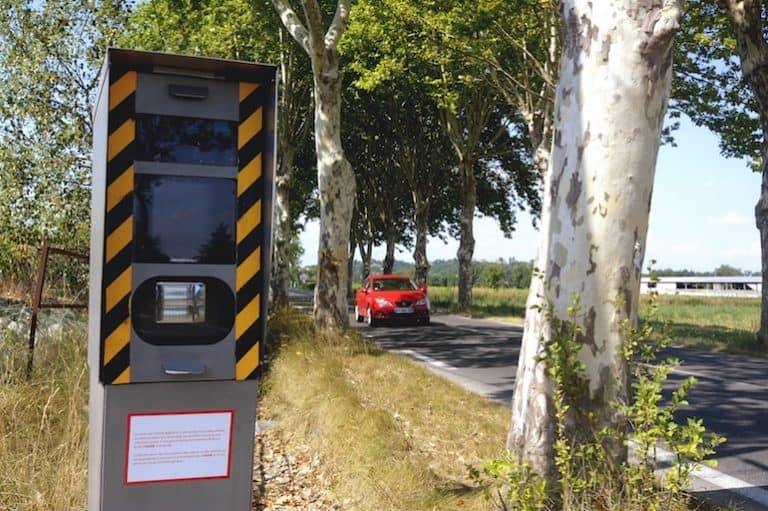 Un radar escondido detrás de un árbol