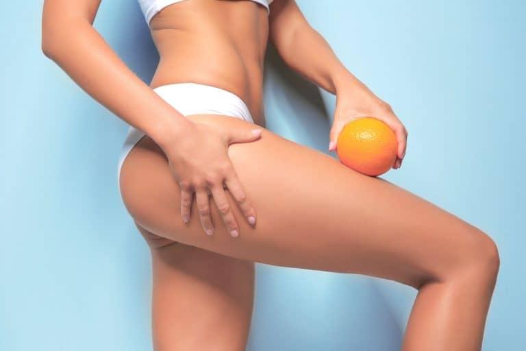 Una mujer mostrando una naranja