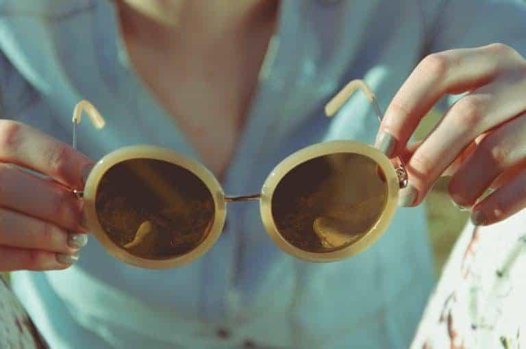 Chica con gafas en sus manos