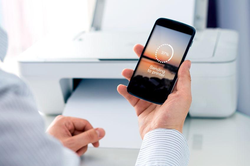 Persona que conecta el teléfono celular a la impresora