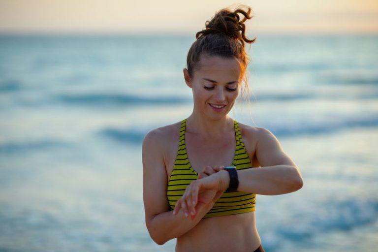 mujer en la playa haciendo ejercicio mirando el reloj