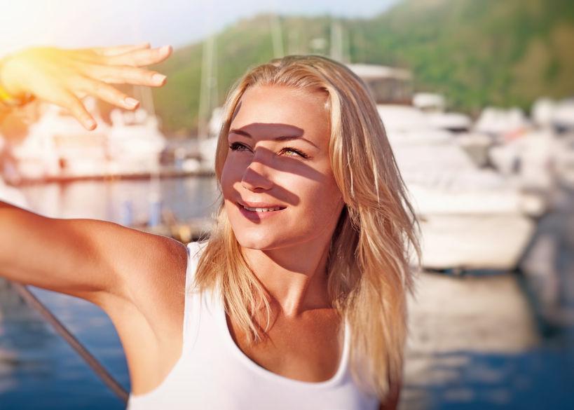 Mujer cubriendose la cara de los rayos del sol