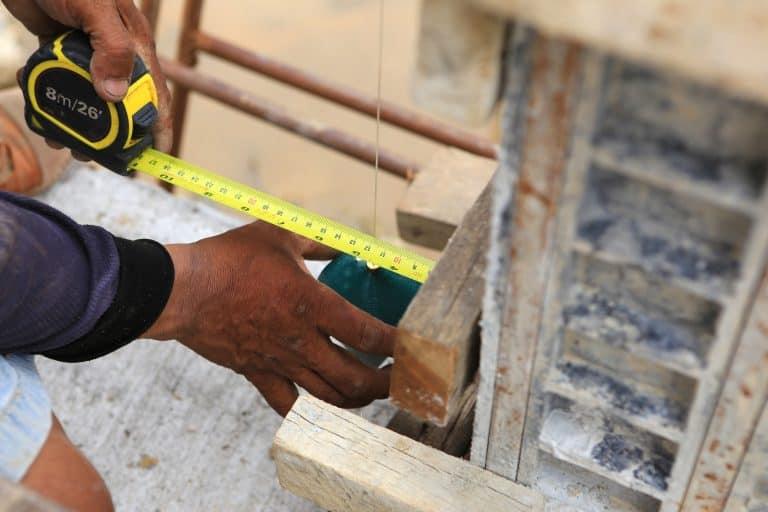 Un obrero midiendo con una plomada
