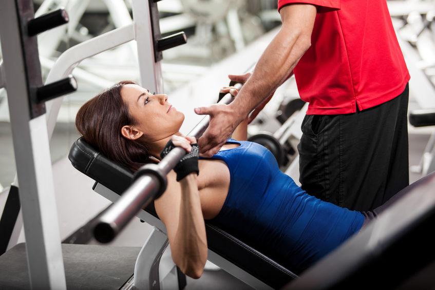 Imagen de una mujer levantando pesa ayudada por instructor en gimnasio