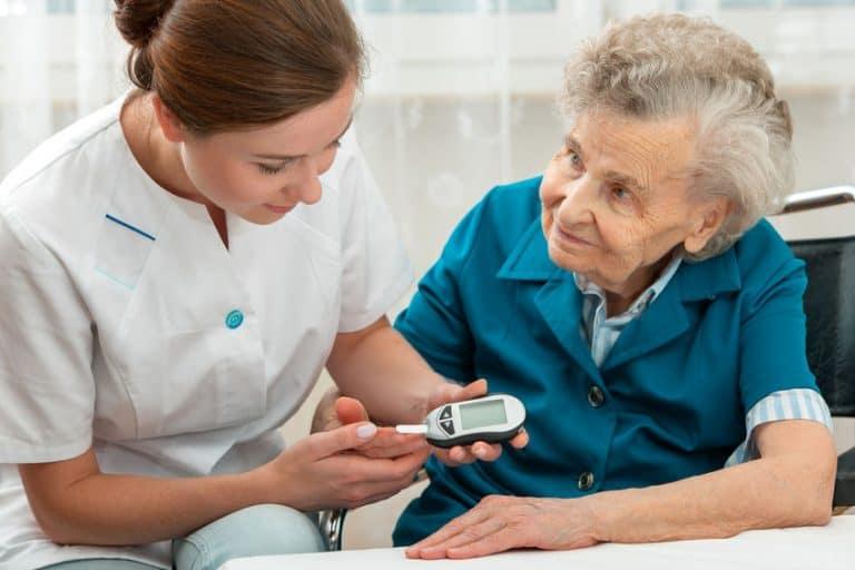 Enfermera midiendo la sangre de anciana