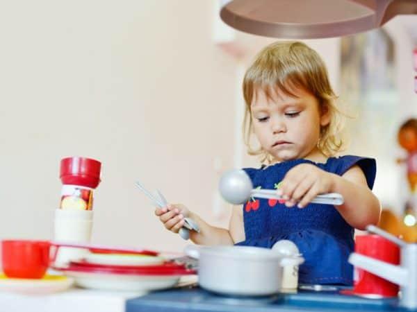 Niña jugando con juguetes de cocina