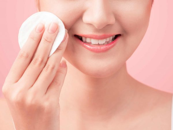 Gorgeous young woman holding cotton pad and smiling in taking care of her face for fresh healthy skincare on pink background