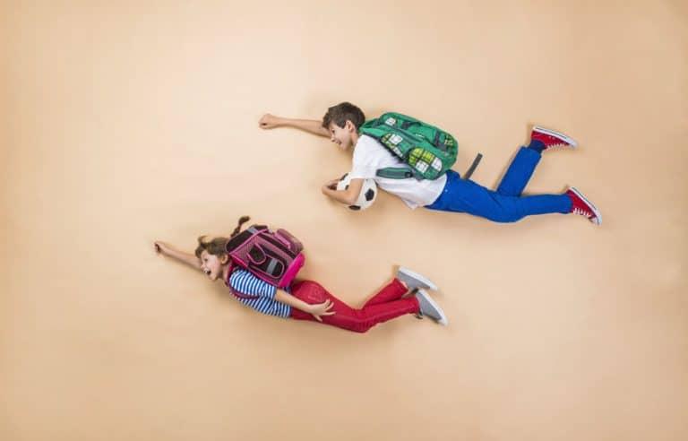 Dos niños con mochilas haciendo que vuelan