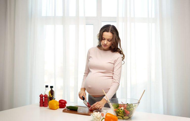 Una mujer embarazada preparando una ensalada