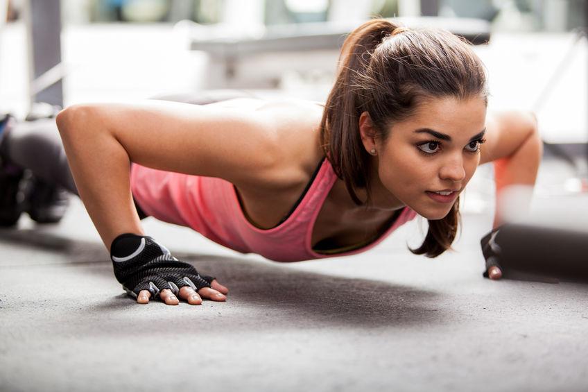 Mujer haciendo flexiones utilizando guantes de gimnasio
