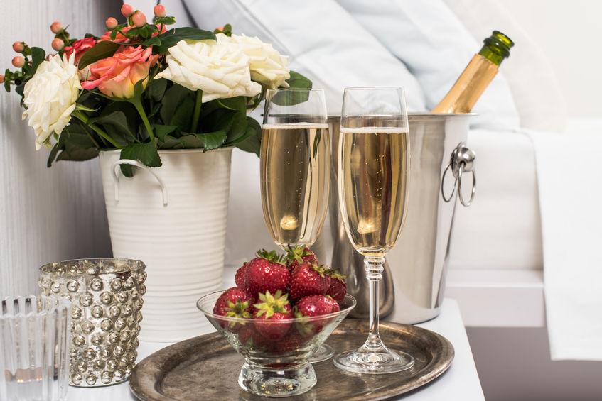Champagne en la cama en una habitación de hotel, cubo de hielo, vasos y frutas sobre lino blanco