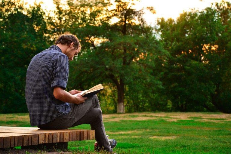 Hombre leyendo libro en el parque