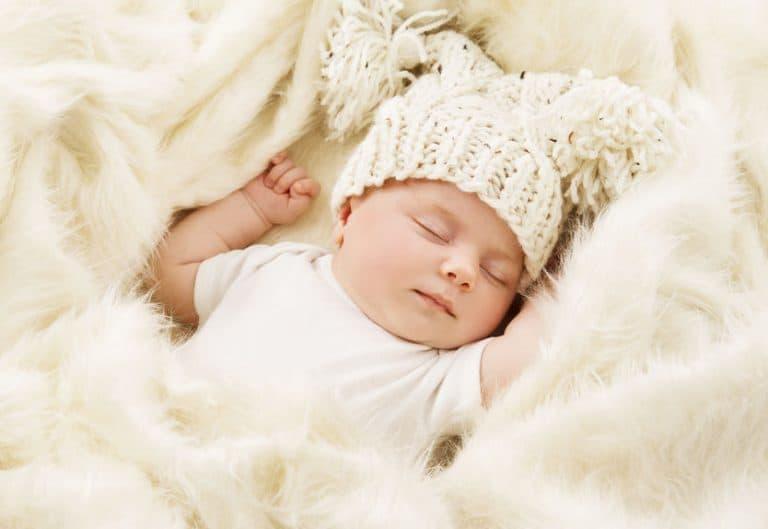 Bebé duermiendo con manta blanca