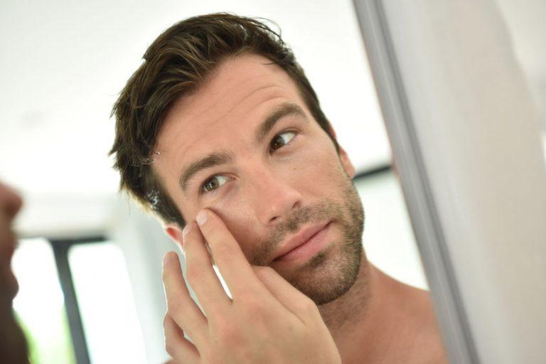 Hombre aplicando crema en su rostro