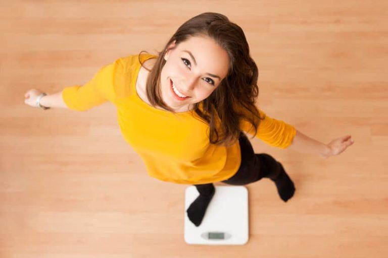 Una mujer con jersey amarillo subida a una báscula