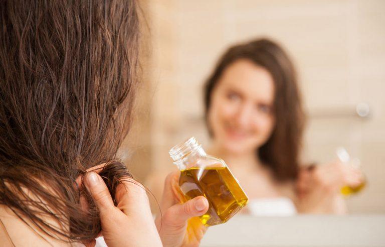 Mujer aplicandose aceite en el pelo