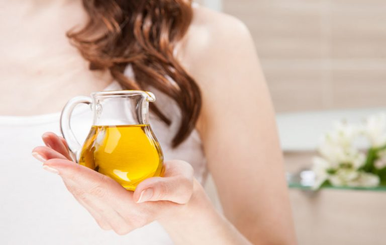 Mujer posando con aceite en envase de vidrio
