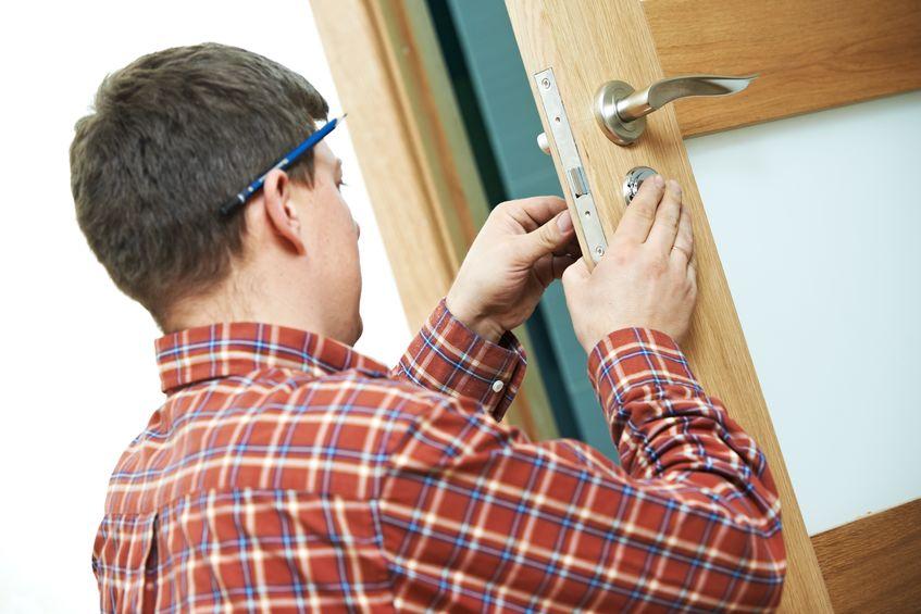carpintero en la instalación de la cerradura de la puerta