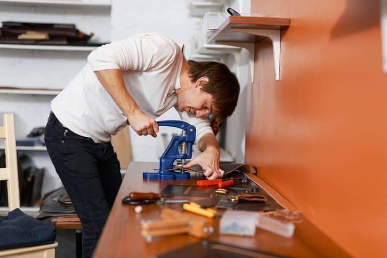 Un trabajar usando una remachadora