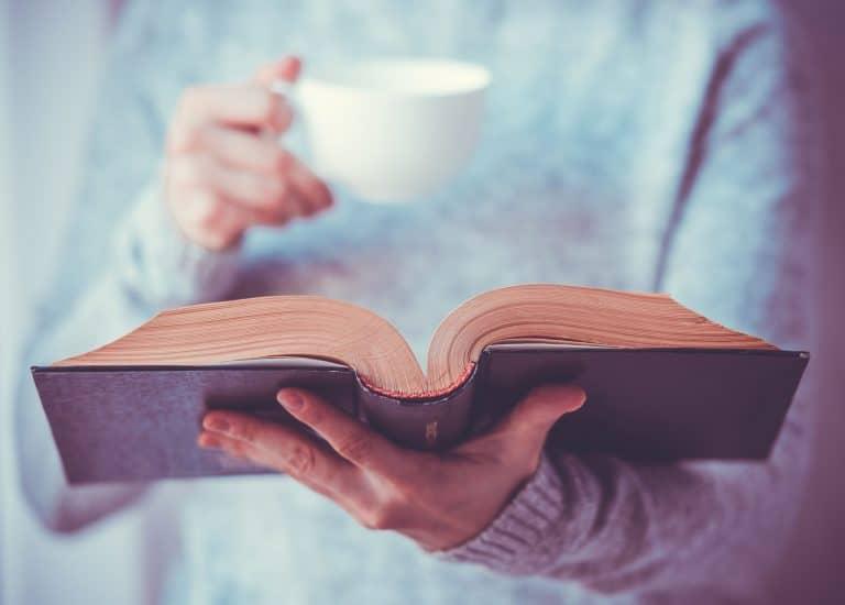 Una mujer leyendo y tomando una taza de té
