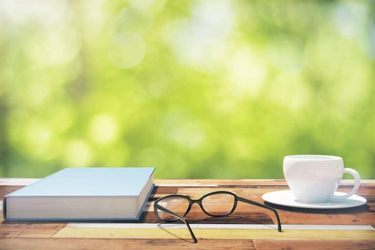 Un libro en una mesa con unas gafas y un café