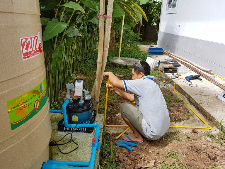 Hombre asiatico instalando bomba de agua