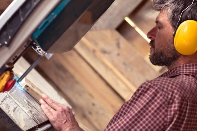 Carpintero trabajando con sierra de cinta