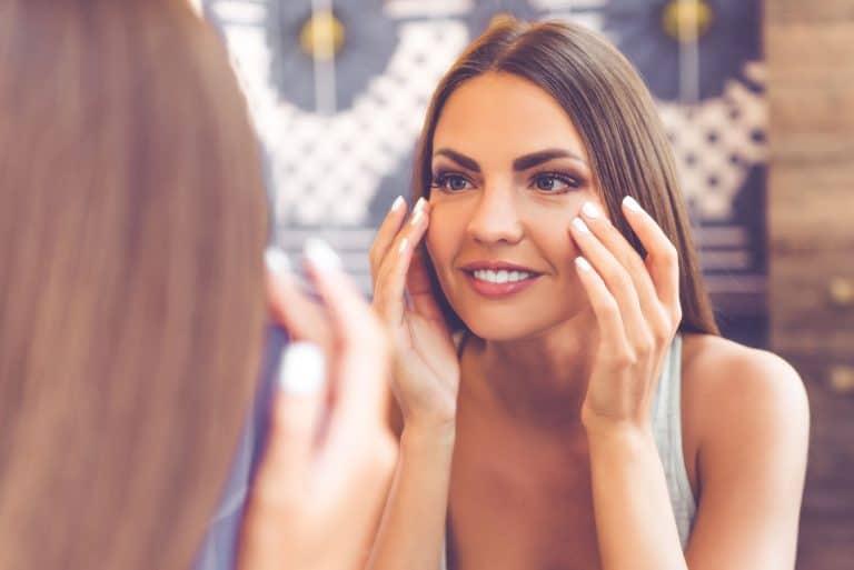 mujer aplicando crema en su cara