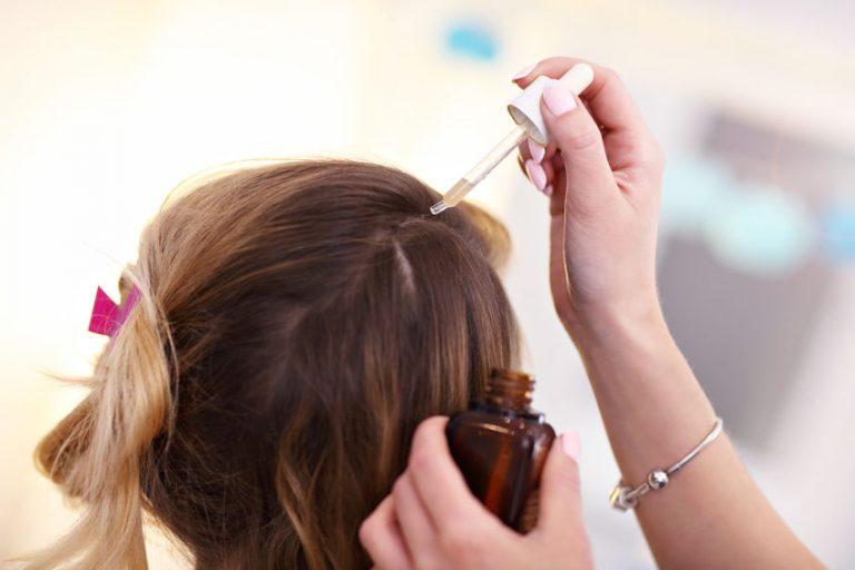 Estilista aplicando aceite para el pelo en cliente