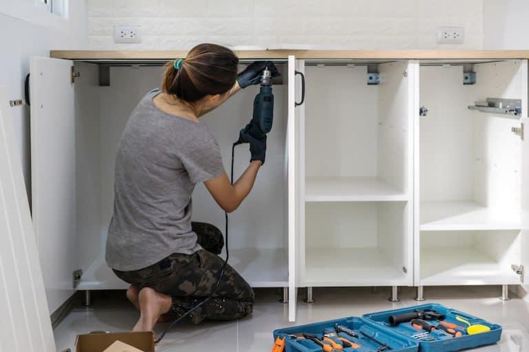 Una mujer trabajando con un taladro