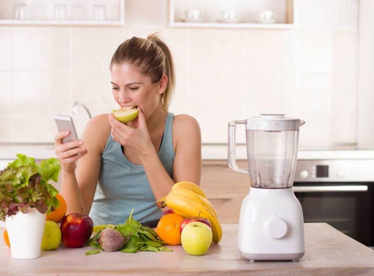 Una mujer con una batidora y fruta