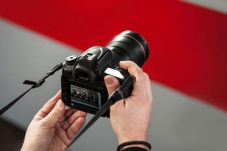 Hombre sosteniendo cámara profesional