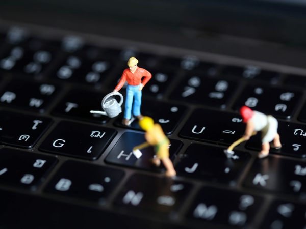 Miniature people : worker team with  button on a computer keyboard.