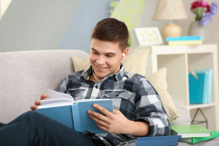 Hombre escuchando su audiolibro en sillón