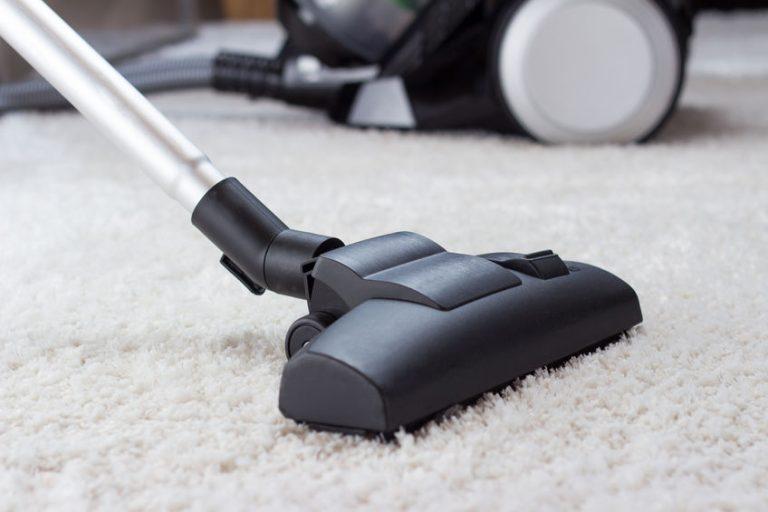 Aspirador en alfombra blanca
